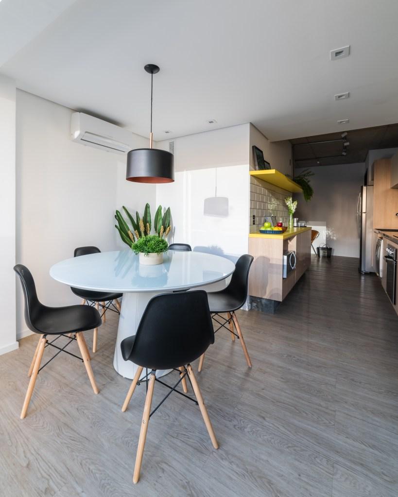 Cozinha co estilo industrial, com mesa brnca e quatro cadeiras com assento preto e pés de madeira. O chão é de madeira cinza e as paredes são branca. Na mesa, um vaso pequeno com planta e acima dela um pendente com cúpula redonda vazada em cima e embaixo