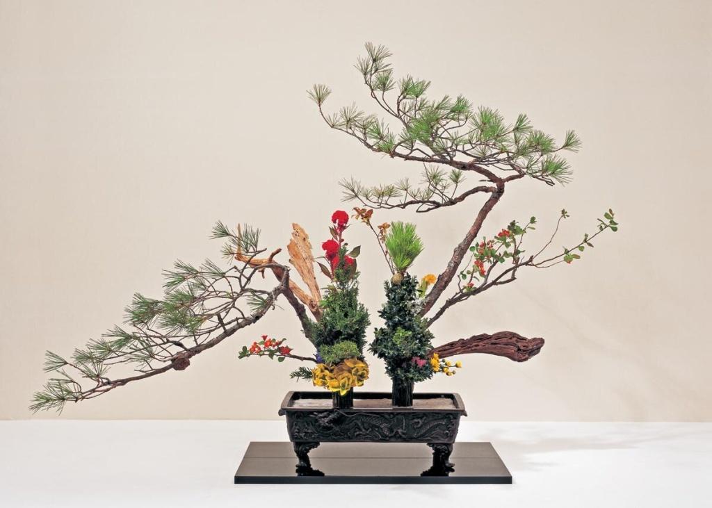 Ikebana com dois troncos, dois galhos e flores vermelhas e amarelas