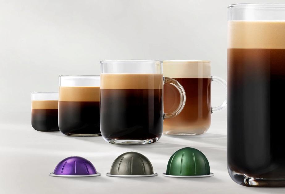 Cinco xícaras de vidro com cafés em diferentes tamanhos. Três cápsulas com diferentes tamanhos