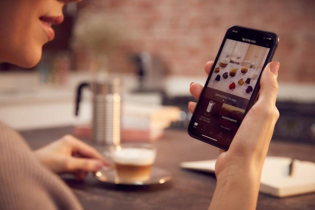 Mulher segurando celular com aplicativo da Nespresso aberto. Xícara de café na outra mão