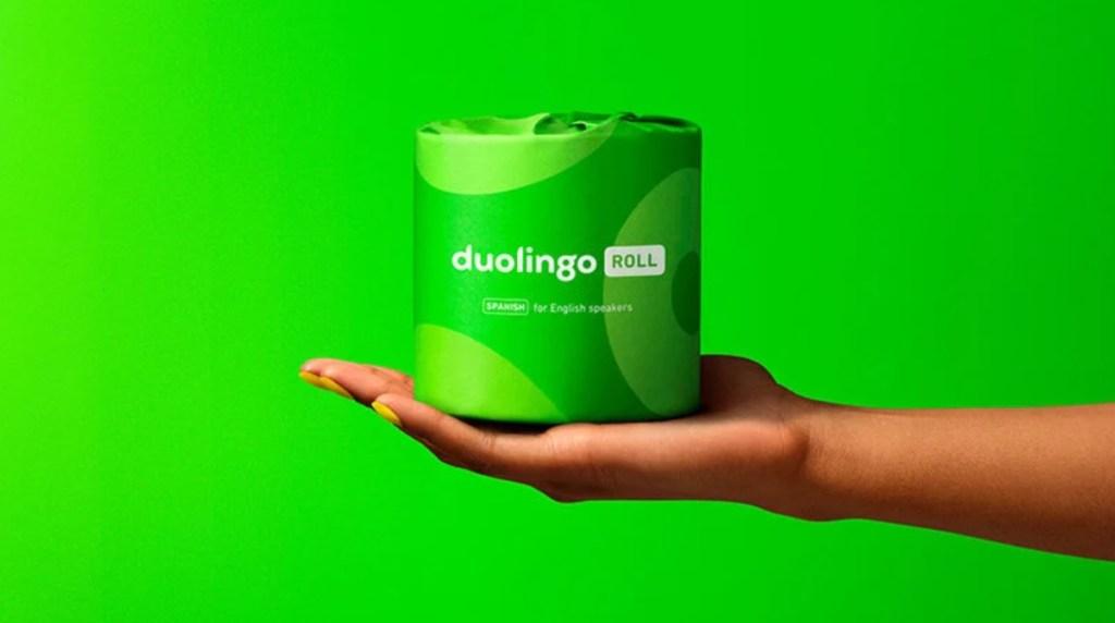 Rolo de papel higiênico fechado verde segurado por mão