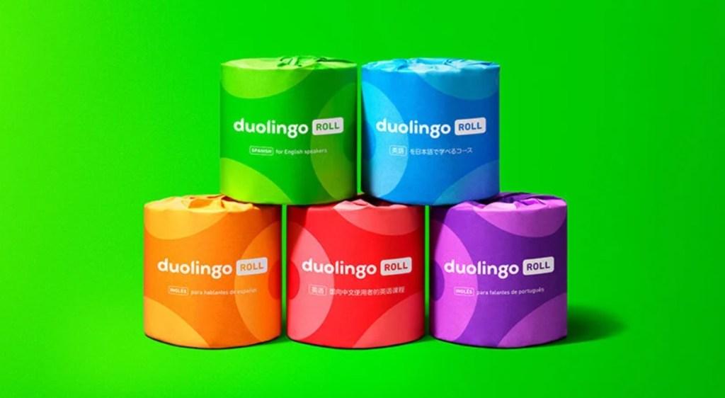 Cinco rolos de papel higiênico da Duolingo empilhados. Um verde, um azul, um laranja, um vermelho e um roxo
