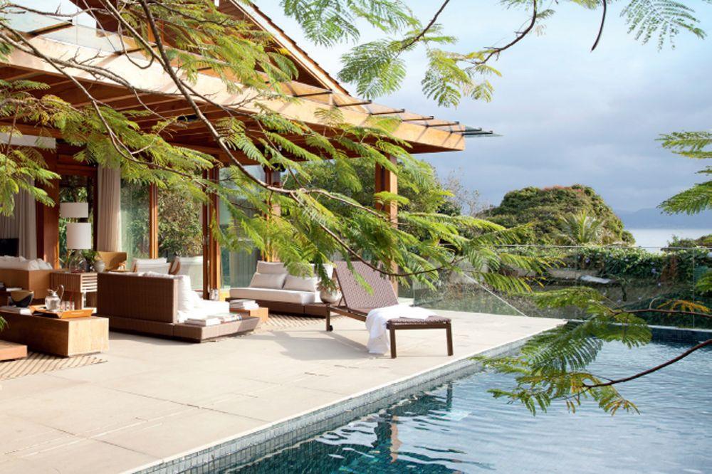 Pergolado de madeira no ambiente externo de uma casa com piscina e muitas árvores