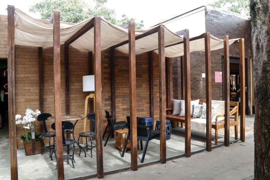Pergolado de madeira no ambiente externo de um restaurante, com mesas e cadeiras pretas.