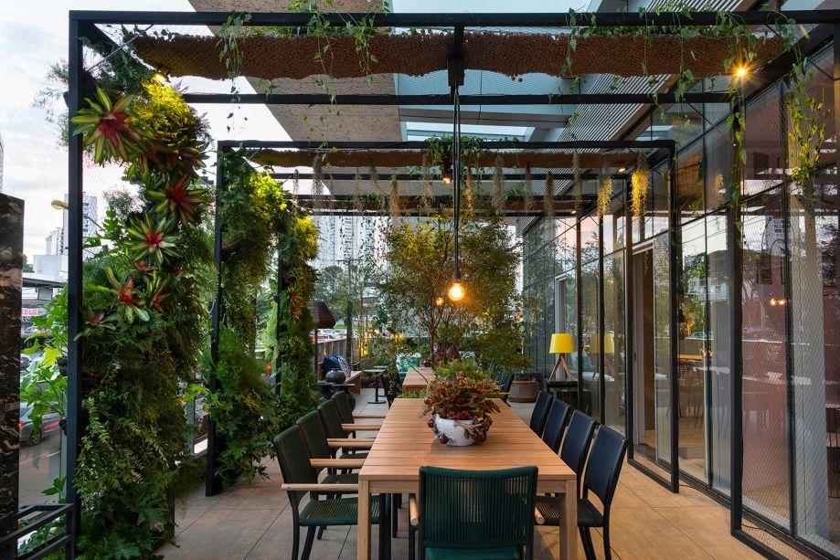 Jardim com mesa e plantas trepadeiras na pérgola de madeira.