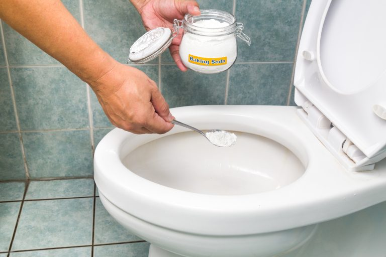 Mão colocando biacrbonato de sódio em vaso sanitário branco