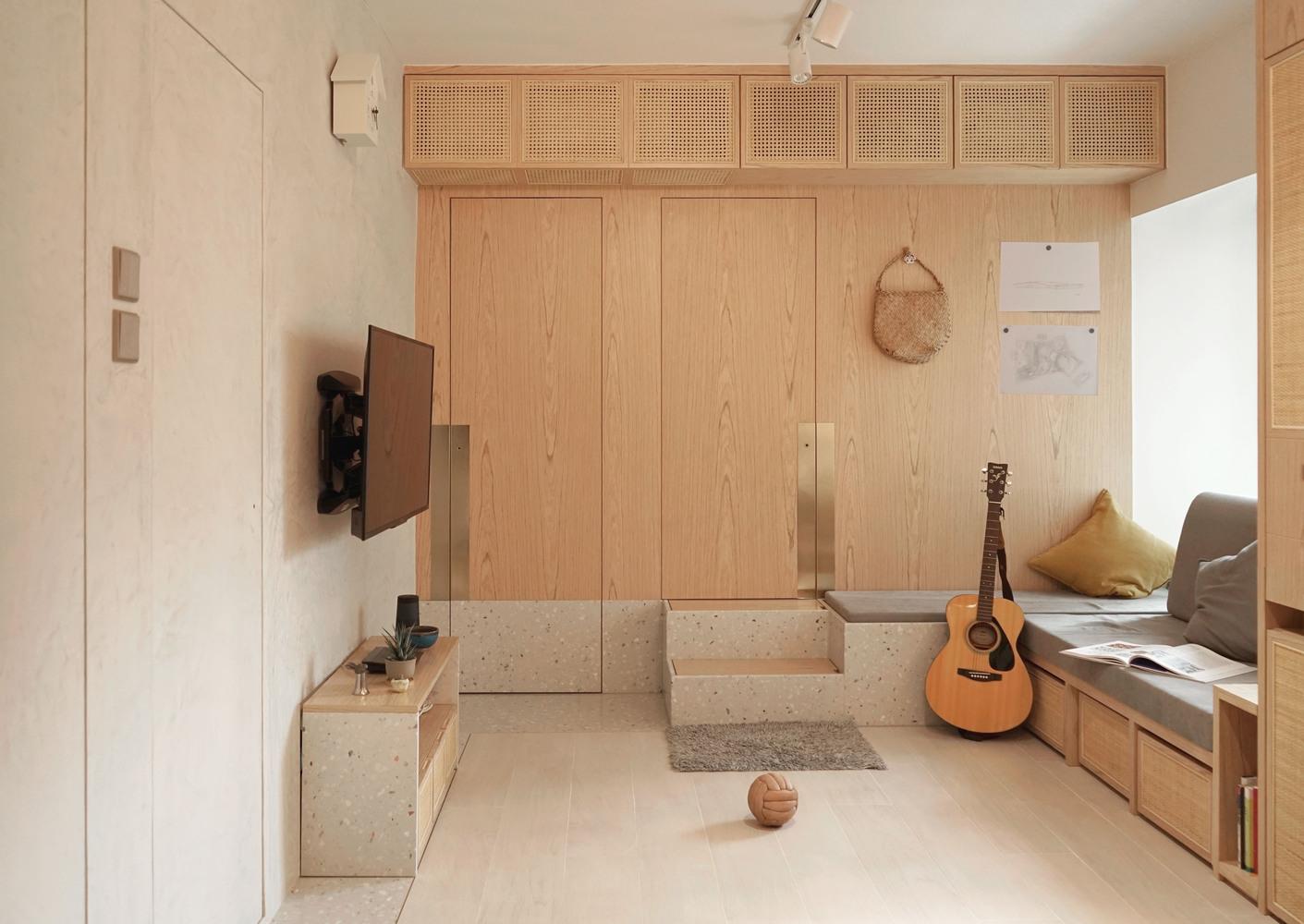 Sala com canto alemão do lado direito. À frente, portas em madeira que se camuflam na parede. Tv na parede. Violão encostado no sofá