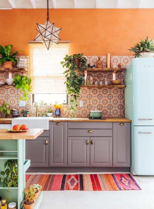 Cozinha com paredes laranjas e azulejos. Luminária em formato de estrela. Balcão cinza. Geladeira azul clara
