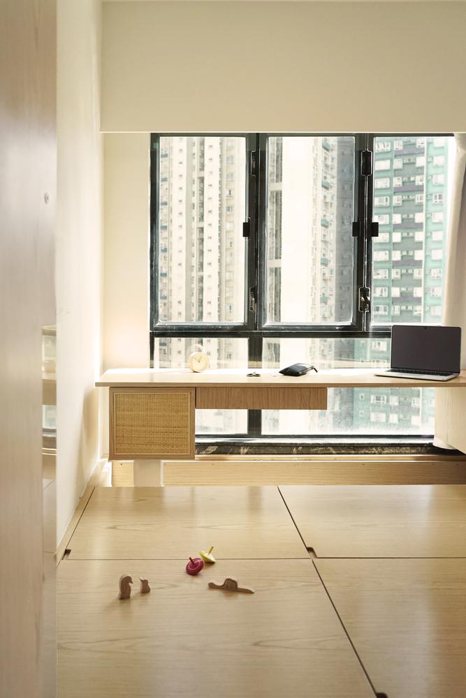 Mesa de escritório em madeira clara. Notebook no canto direito. Grande janela ao fundo