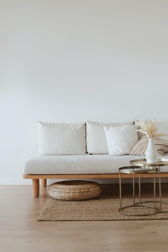 Sofá branco, almofadas brancas, piso de madeira. Mesa de centro em madeira