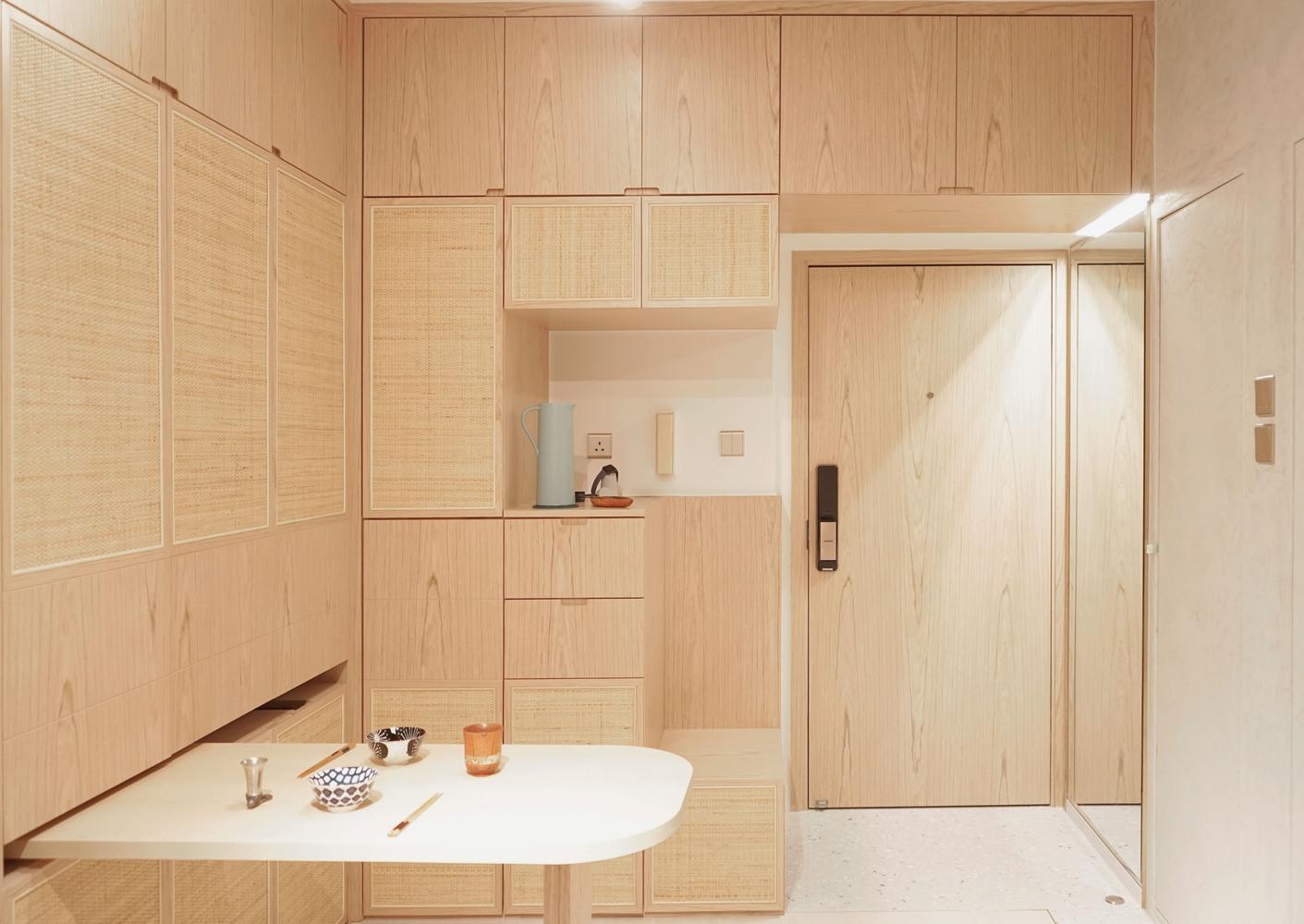 Cozinha em madeira clara e modular. Mesa retrátil branca.