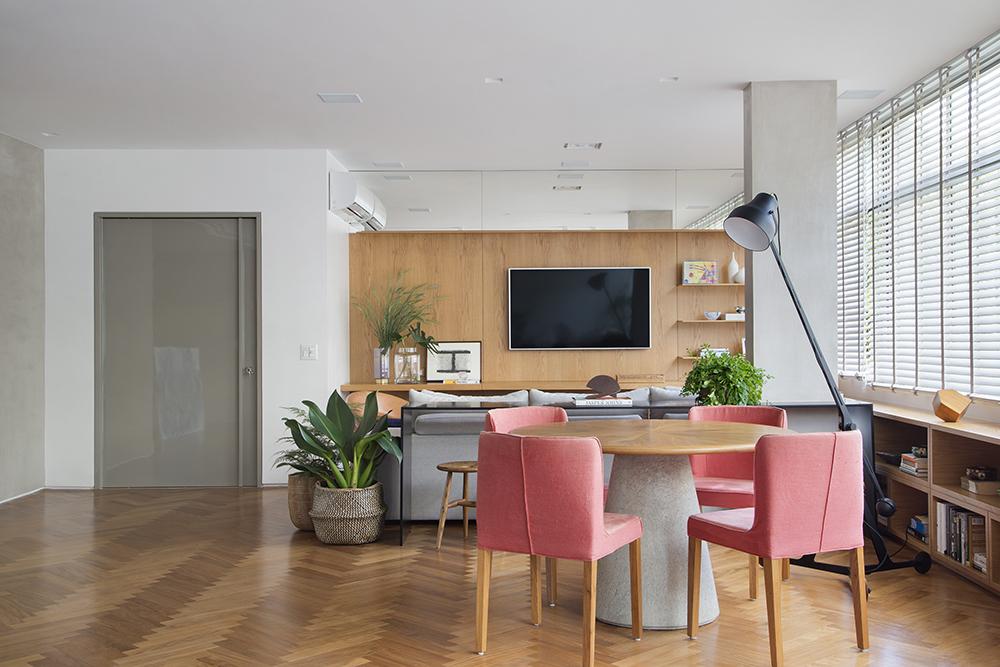 Mesa circular com cadeiras rosa; Sofá cinza. Móvel em madeira com tv