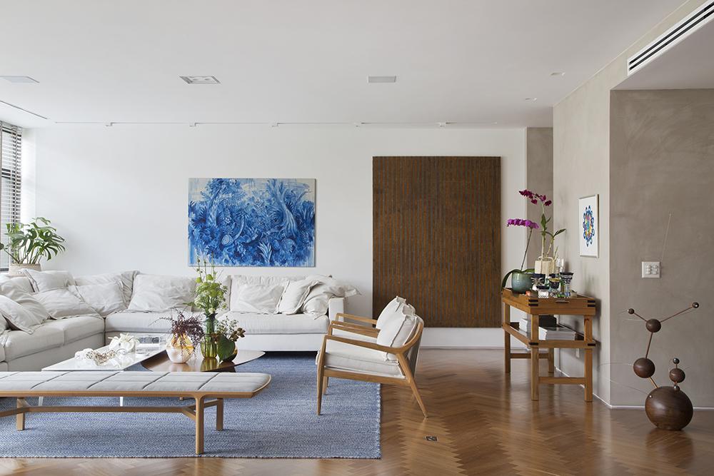 Estar com tapete azul. Sofá branco. Pintura azul e branca na parede.