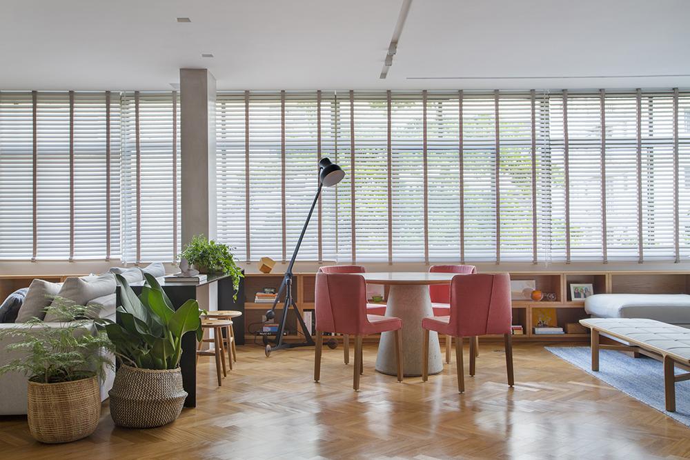 Living com piso em madeira clara. Mesa branca redonda. Cadeiras com estofado rosa goiaba. Janela com persianas no fundo