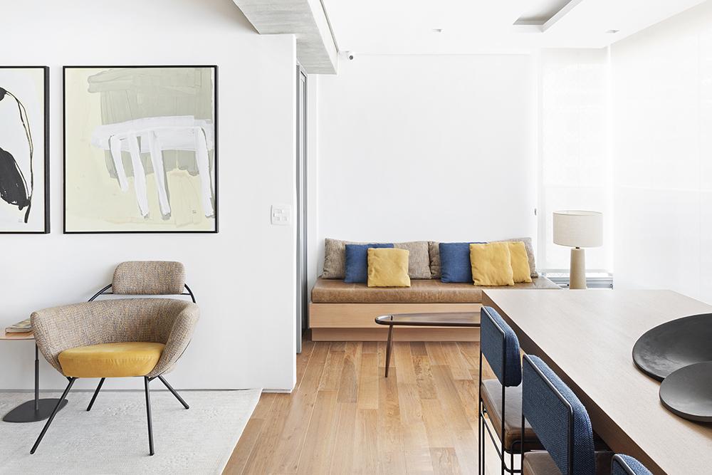 Varanda integrada com sofá em couro marrom claro e almofadas amarelas e azuis encostado na parede. Ponta da mesa de jantar em madeira. Poltrona com almofadas beges e amarelas do lado esquerdo. Quadros abstratos na parede.