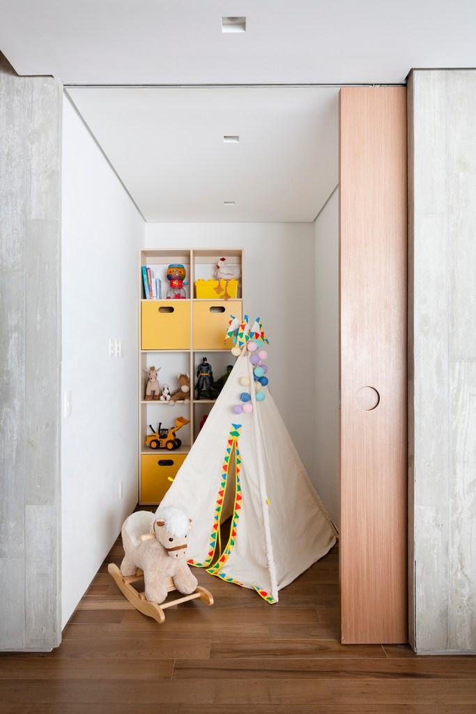 Brinquedoteca atrás de porta de correr em madeira. Pequena cabana com detalhes coloridos. Estante com nichos amarela em madeira com brinquedos. Cavalinho de brinquedo à frente.