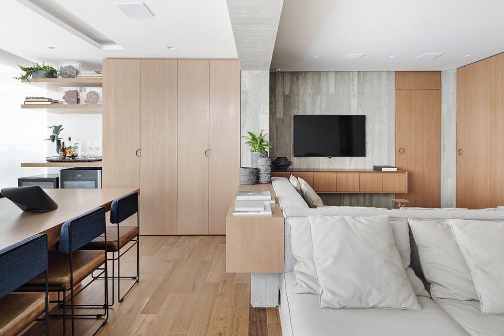Living integrado com sofás claros e móveis e piso em madeira. Paredes revestidas de concreto e tv ao fundo