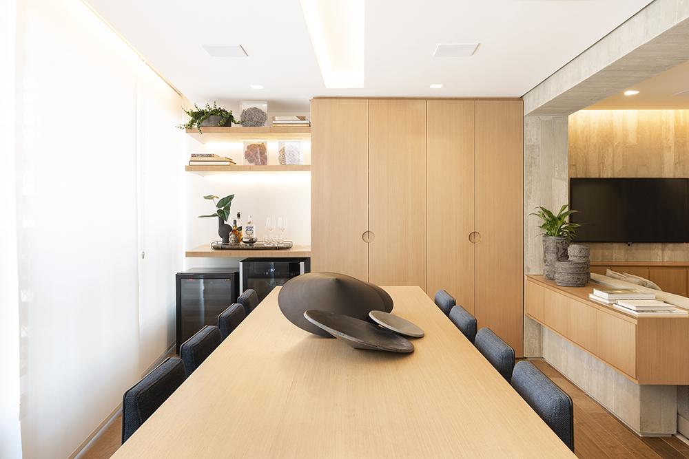 Mesa de jantar em madeira com peças de design em forma de peão preto em cima. Cadeiras com estofado azul marinho. Armário em madeira ao fundo