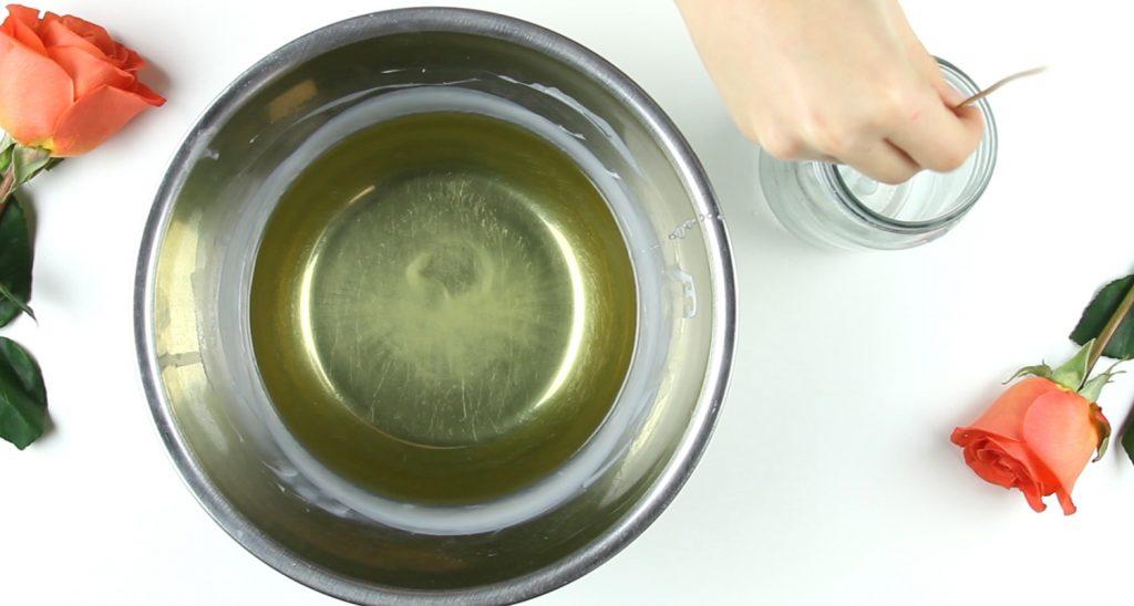Cera derretida em recipiente. Mãos posicionando pavio em frasco de vidro.