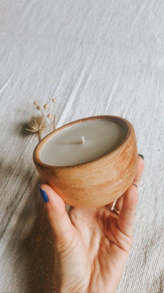 Mão segurando vela com suporte marrom circular