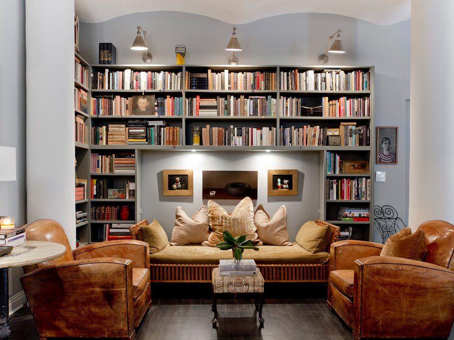 Sala com duas poltronas marrons, sofá marrom com estrutura em bambu. Estante na parede envolvendo o sofá. Três luzes iluminam a estante