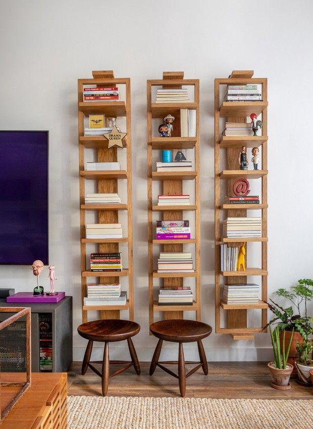 Três estantes estreitas em madeira. Livros e bonequinhos nas prateleira