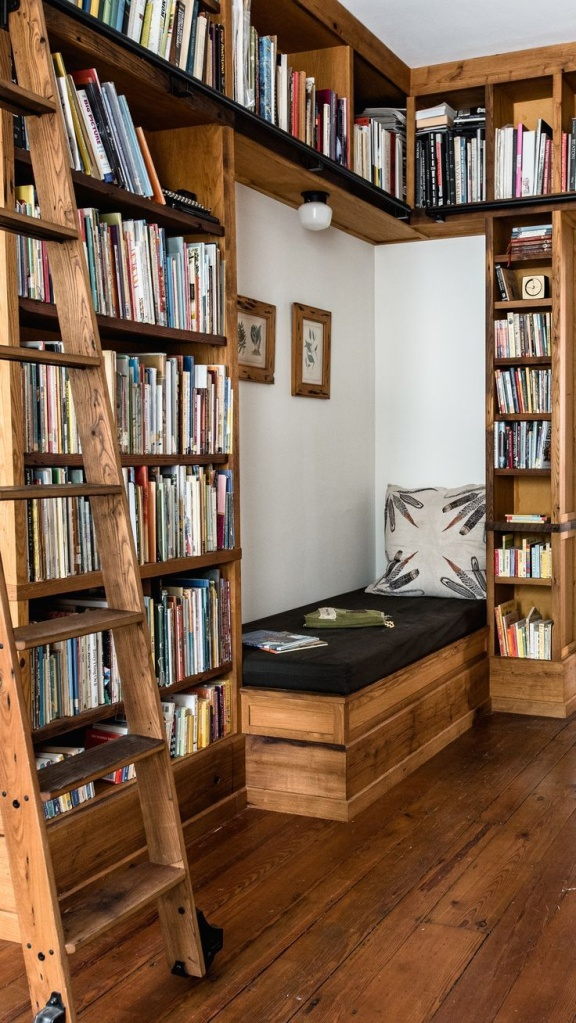 Estante em madeira rústica com escada. Espaço para sofá com almofada preta.
