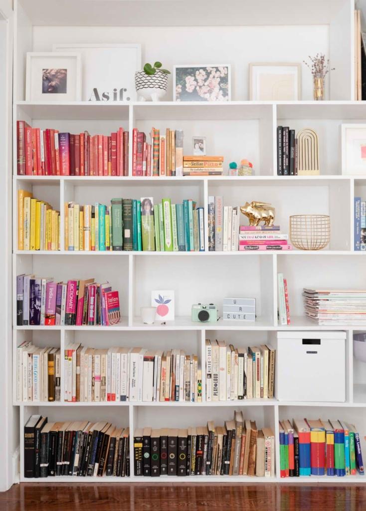 Estante branca com nichos e livros organizados por cor