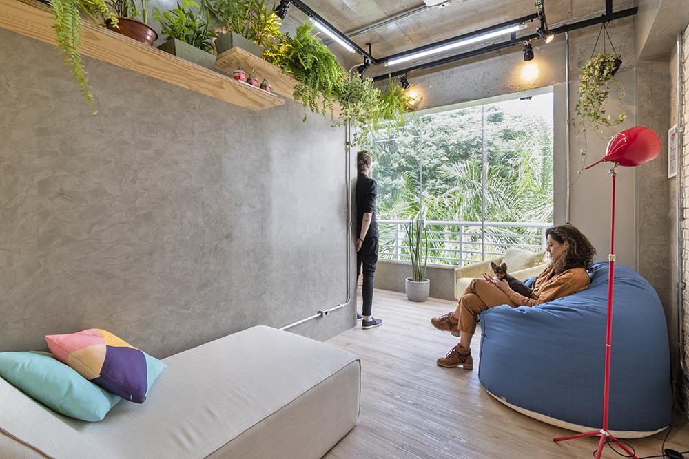 Espaço de relaxamento com sofá cinza. Puff azul grande. Paredes em concreto. Prateleiras com plantas. Janela grande