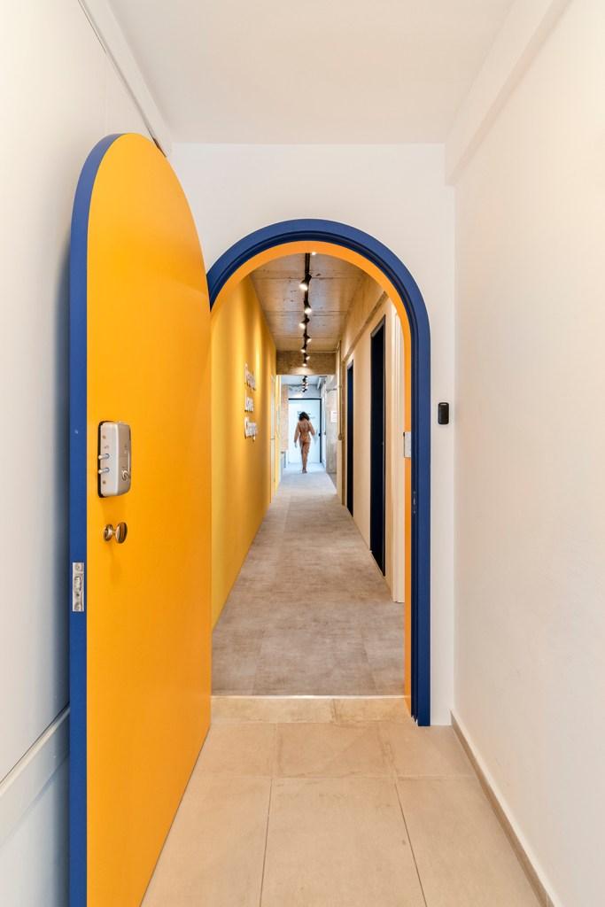 Corredor com paredes amarelas. Porta azul escura com uma das faces amarelas.