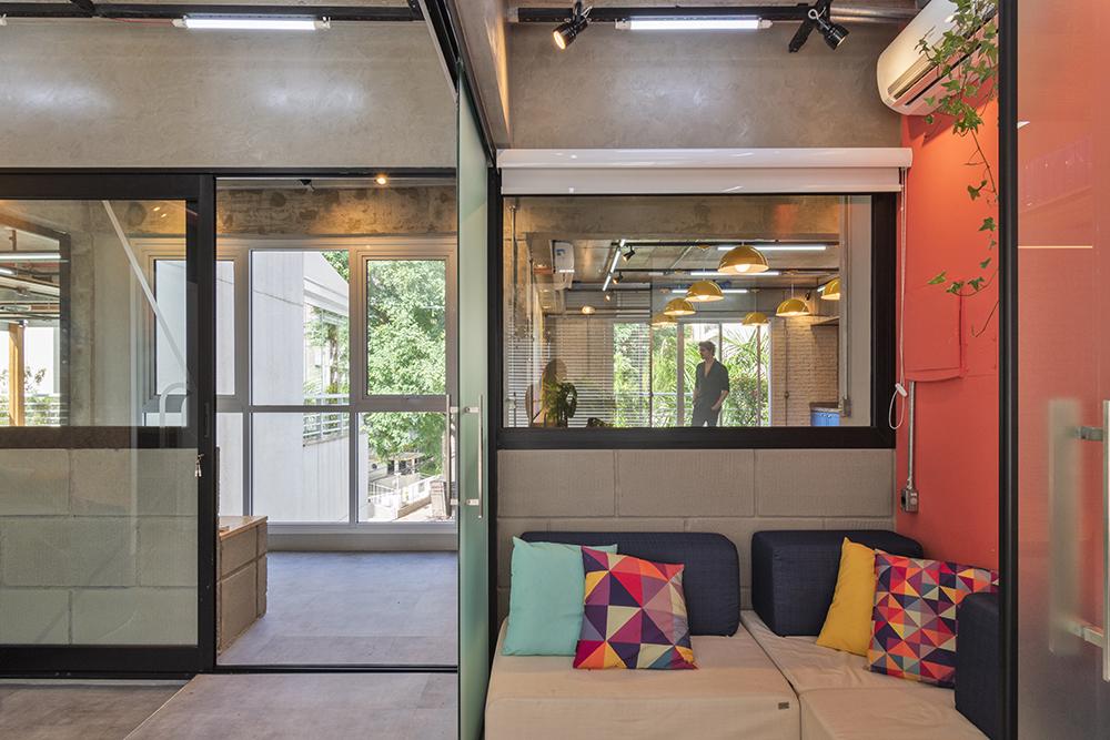Sala com paredes em vidro. Sofá acinzentado. Almofadas azuis escuras e outras com padrões geométricos coloridos.