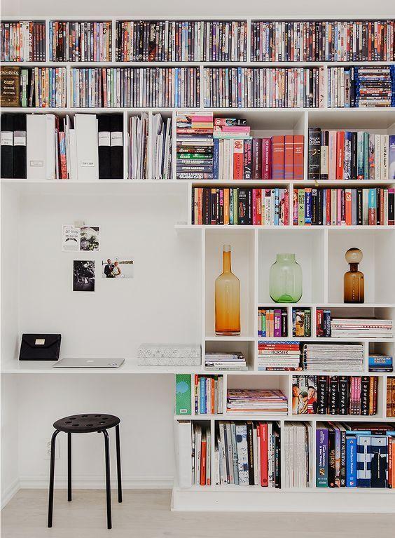 Estante branca com nichos e um espaço maior para computador. Vasos, livros e dvds na parte superior