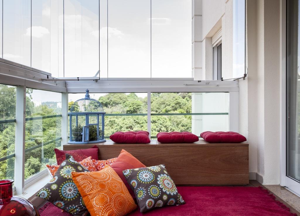Varanda com baú em madeira com almofadas vermelhas. Almofadas laranjas e marrons com estampas de círculo no chão sobre tapete vermelho.