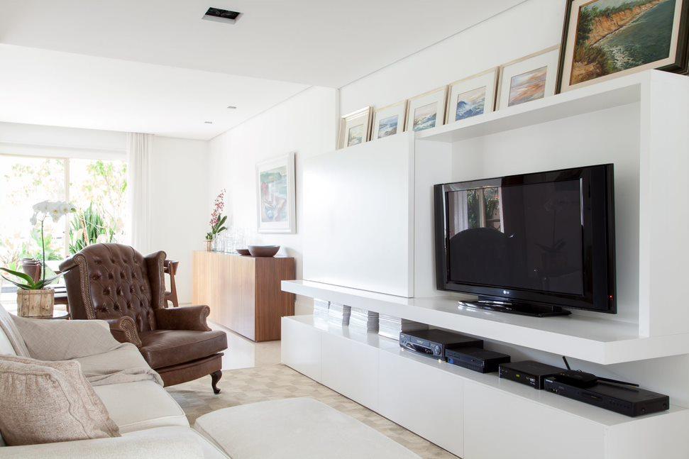 Sala de tv com hack branco. Quadros apoiados na parte de cima do hack. Poltrona em couro marrom e sofá branco.