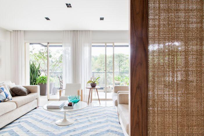 Porta de deslizar em fibra natural emoldurada por madeira em primeiro plano. Living com tapete branco e azul e sofá ao fundo.