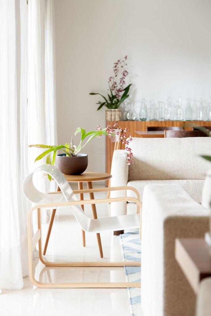 Cadeira branca. Sofá bege. Mesa lateral em madeira com orquídeas