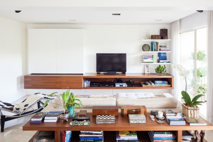 Sala de tv com sofá bege e parede branca com prateleiras brancas. Hack em madeira. Aparador com livros encostado na parte de trás do sofá.