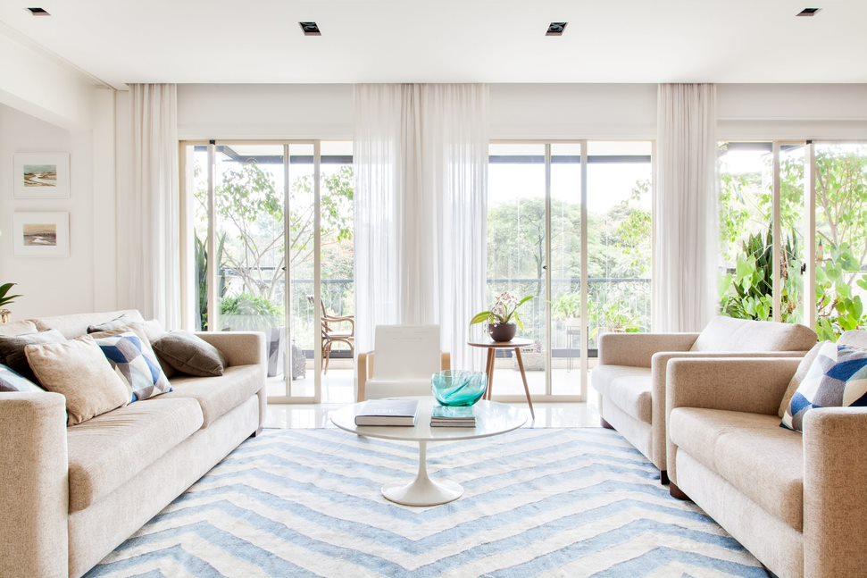 Living com tapete branco e azul e sofás beges. Ao fundo, grandes portas de vidro com árvores à vista