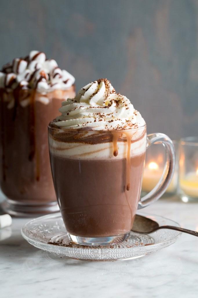 Xícara de vidro com chocolate quente escorrendo do lado