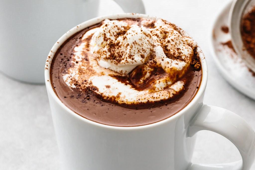 Caneca branca com chocolate quente e chantilly em cima