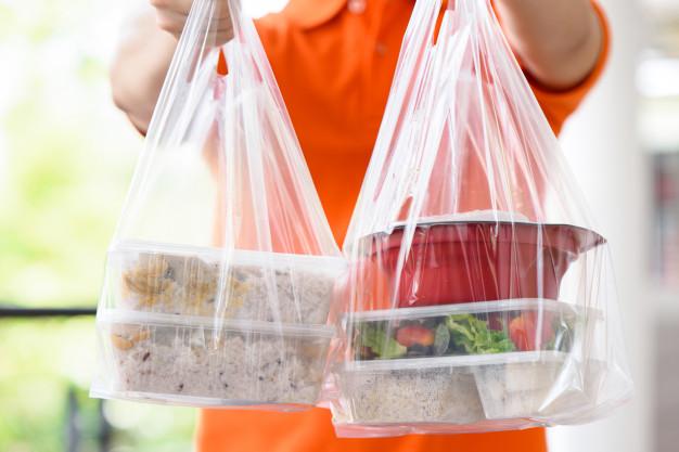 Homem de camisa laranja entregando duas sacolas transparentes com marmitas transparentes dentro.