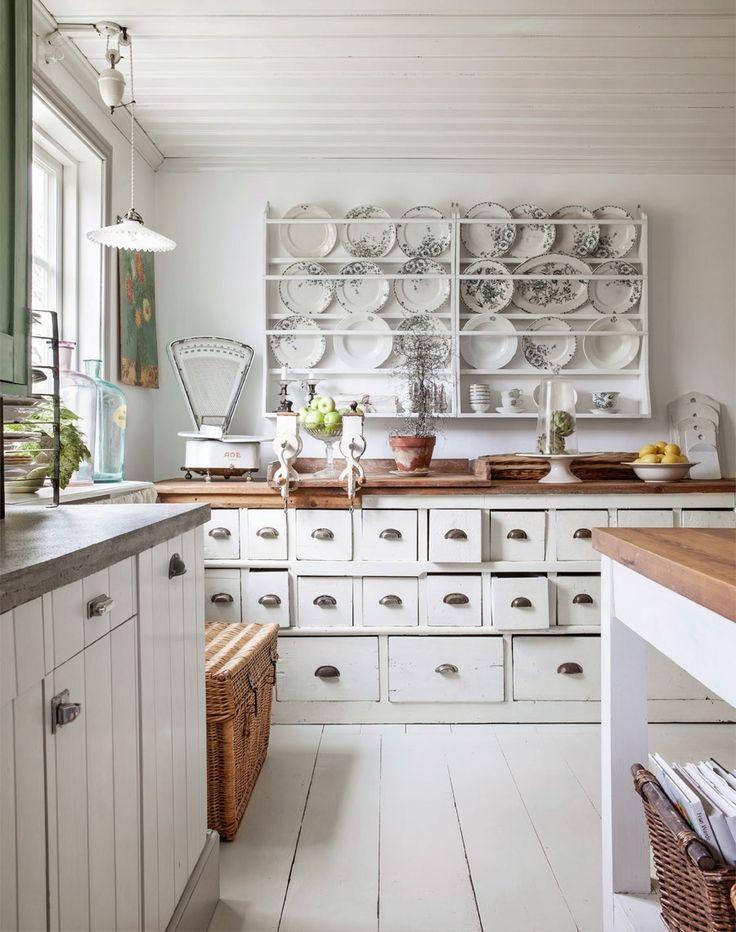 Cozinha com bancadas em madeira branca embaixo e topo em madeira escura. Pratos com flores em prateleiras na parede. Balança rústica, maçãs e peras na bancada.