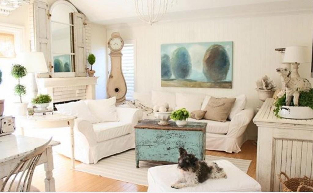Living com dois sofás brancos. Mesa rústica azul de centro. Cachorro sentado no puff branco. Aparador em madeira branco. Piso em madeira. Relógio ao fundo.