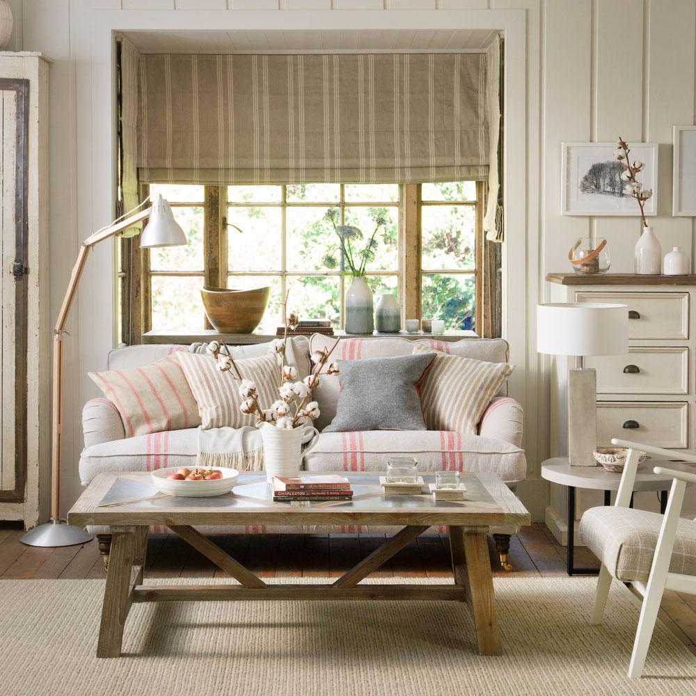 Living com sofá claro e listras vermelhas. Mesa em madeira. Tapete bege. Aparador em madeira branca