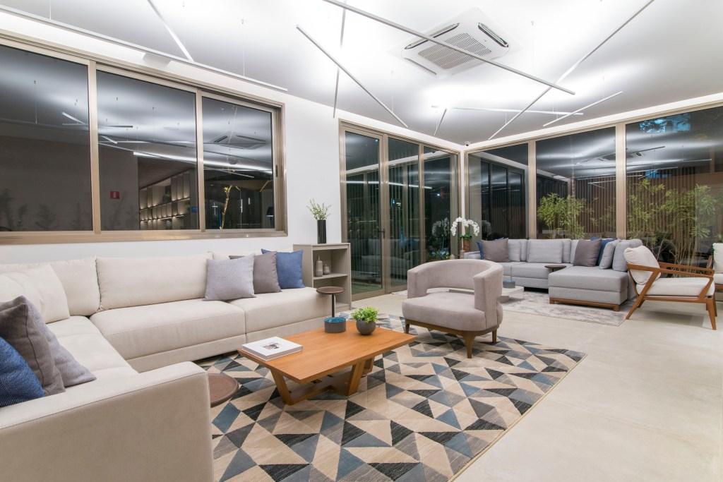 Lounge com tapate geométrico sofá branco e sofá cinza ao fundo