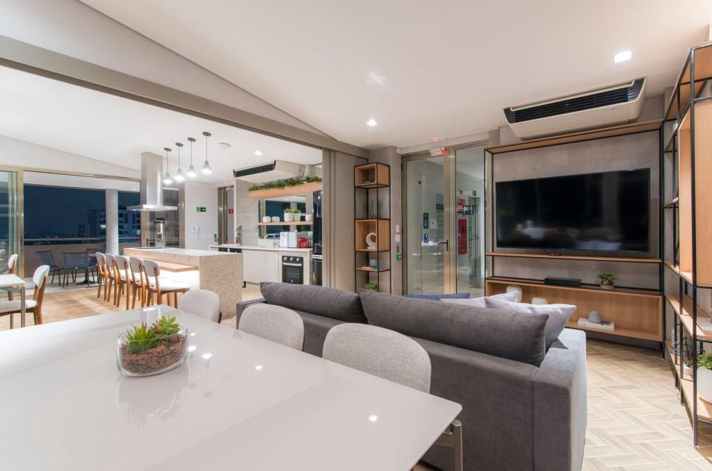Apartamento com living e cozinha integrados. Living com sofá cinza e estante em madeira vazada com tv. Ao fundo, bancada com cadeiras.