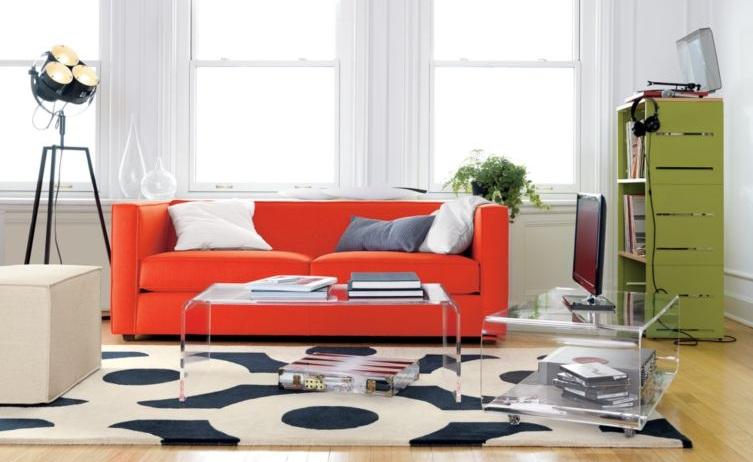 Estar com sofá vermelho. Estante verde. Tapete branco e preto. Duas mesas de centro de acrílico