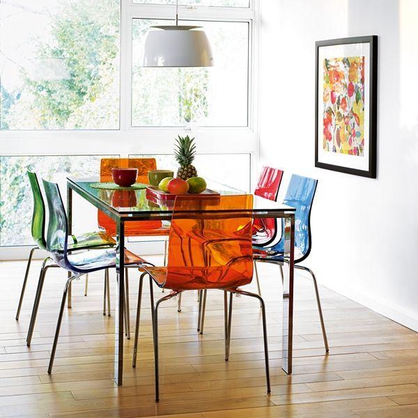 Sala de jantar com seis lugares. Cadeiras laranjas, azuis, vermelhas e verdes. Grande janela ao fundo