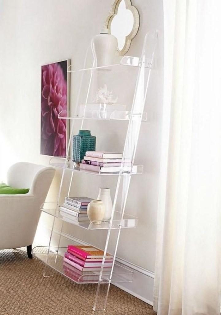 Estante do tipo escada de acrílico incolor apoiada em parede branca. Livros e vasos nas prateleiras