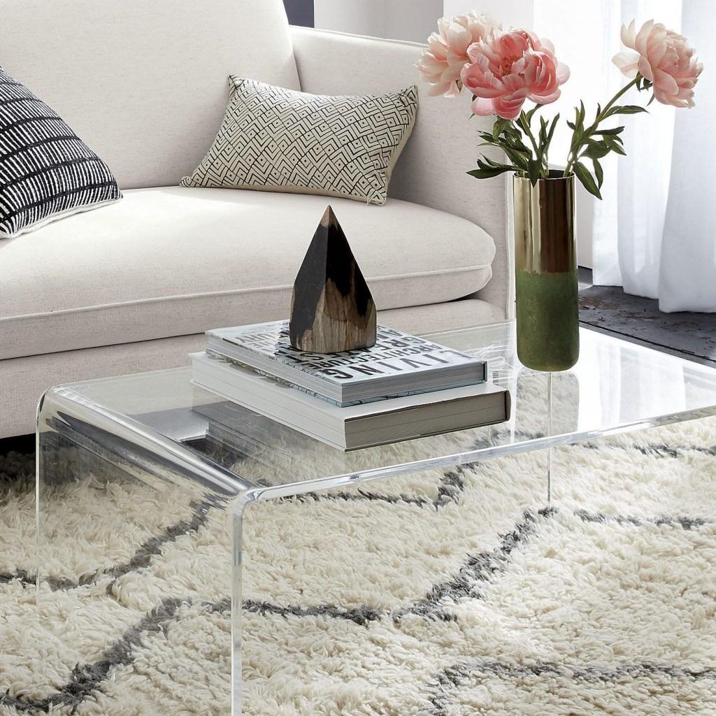 Mesa de centro em acrílico transparente. Livros e vaso de flores rosas. Tapete peludo branco com listras cinzas. Sofá branco.